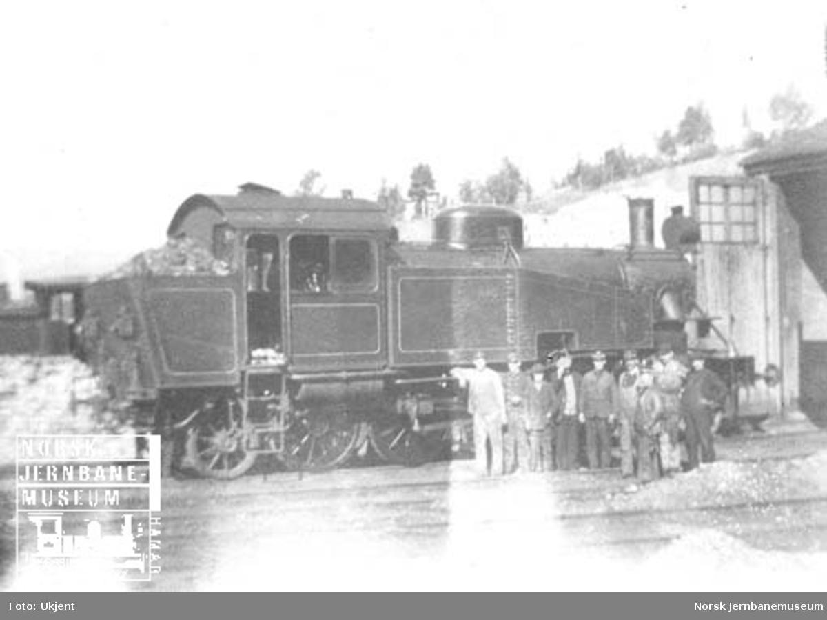 NSB damplokomotiv type 34a nr. 345 med oppstilte jernbanefolk utenfor lokomotivstallen på Dombås
