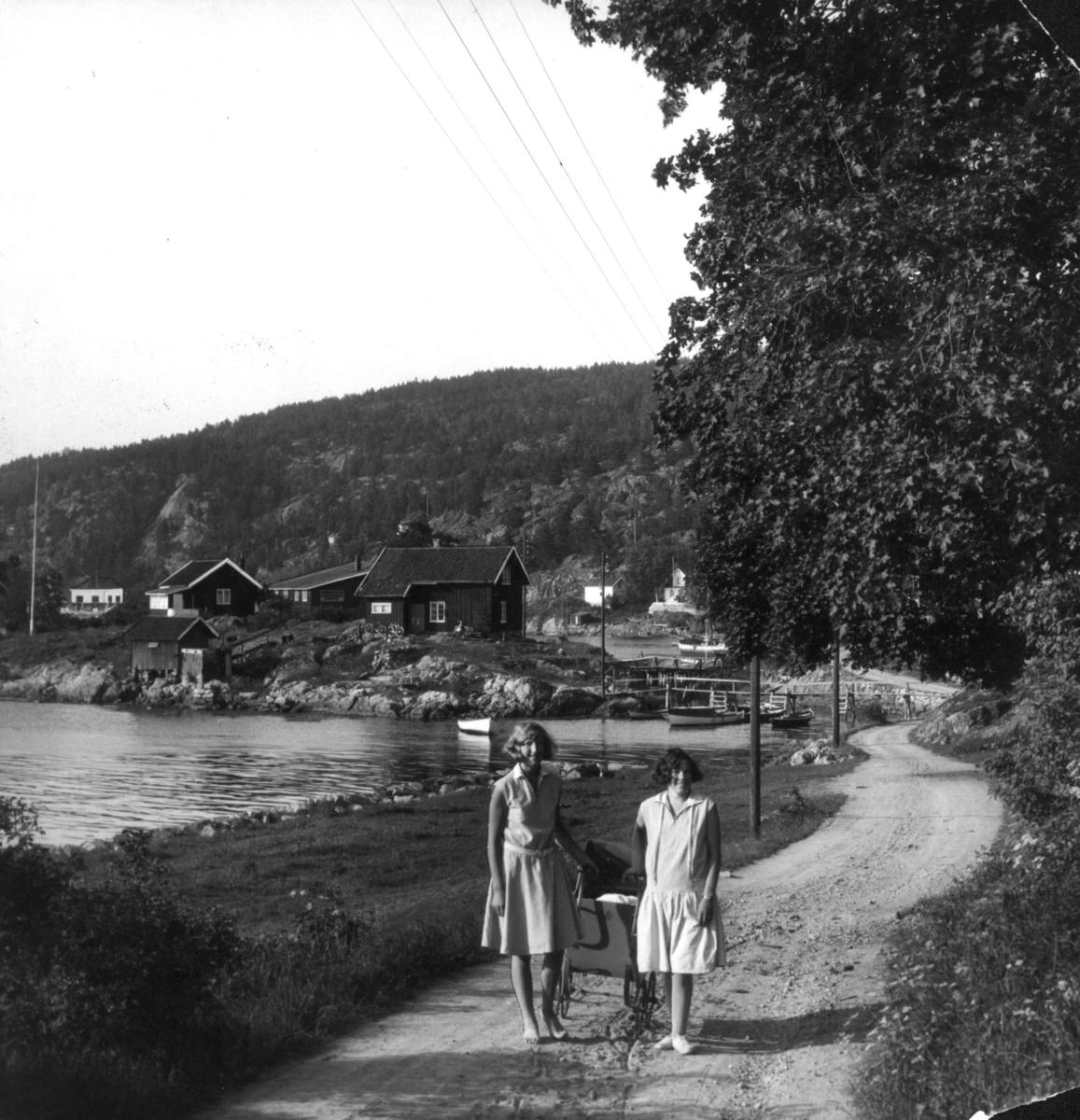 Drøbak, Akershus 1929. To unge kvinner i sommerkjoler med barnevogn står på en vei som går langs sjøen. Bebyggelse og båter ses i bakgrunnen.
