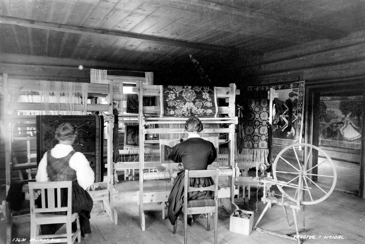 Vevstue med to vevende kvinner. Prestgard, Heidal, Oppland 1935. Vevnader under arbeid. På veggene ferdige tepper. En rokk til høyre i bildet.