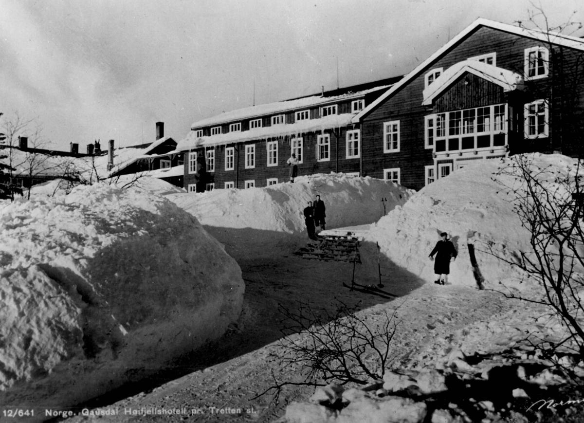 Avfotografert postkort. Fire personer i skitøy med ski og staver satt i snøen utenfor Gausdal høyfjellshotell.