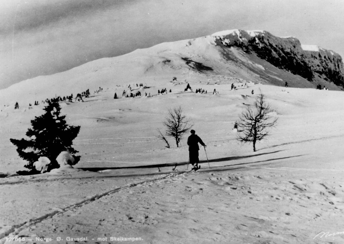 Avfotografert postkort. En enslig skiløper på vei over fjellviddene mot Skeikampen.