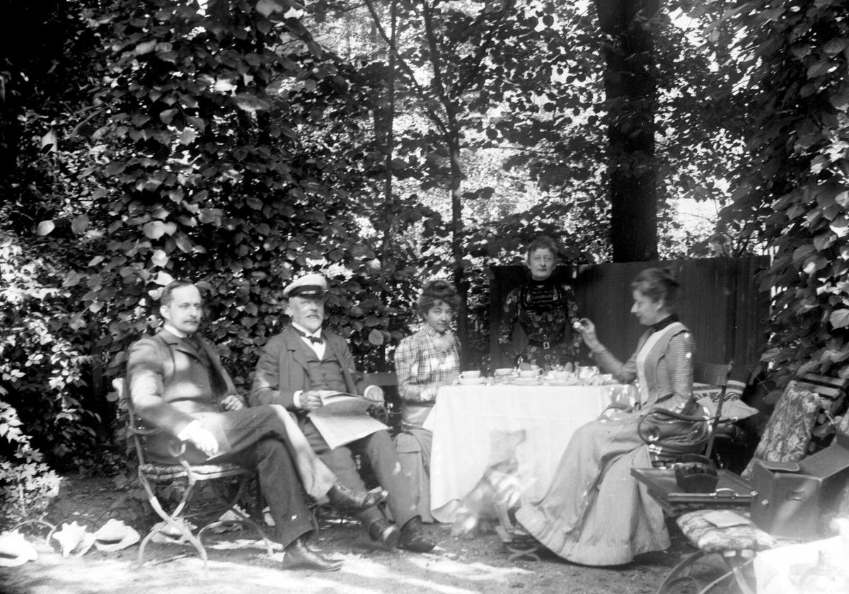 Familiegruppe i hageselskap med dekket kaffebord. Sigrid f. Holm (usikkert om hun er en av de tre kvinnene t.h.), fotografens niese, hos sine svigerforeldre (fam. Hudtwalcker) i Blankenese, Hamburg. Mannen Heinrich (Heini) sitter t.v., deretter  svigerfaren.  Fra malerinne Juliane Fredrikke Langbergs (1856-1930) samling, tatt ca.1895-1910 med motiver fra slekt og venner samt steder tilknyttet samvær med disse.