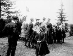 Gruppe med barn og tre kvinner i skogen, ukjent sted.