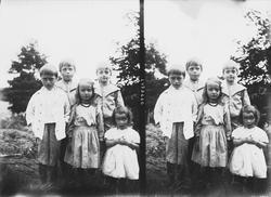 Fem barn oppstilt for fotografering utendørs, ukjent sted.