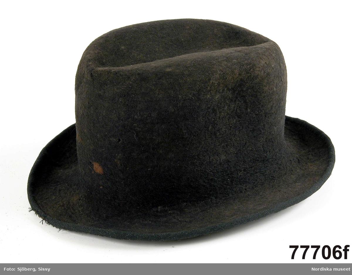 Hel mansdräkt bestående av: a. Tröja, svart kläde b. Väst , rött ylle c. Knäbyxor av sämskskinn d. Strumpor av grått ullgarn e. Halsduk lila/vitt bomullstyg f. Hatt av yllefelb.
