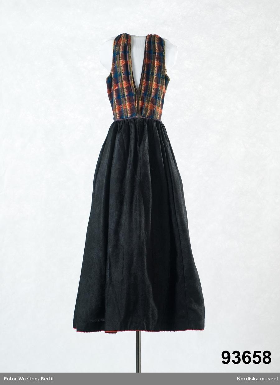 Livkjol med svart kjol av tunt jacquardvävt ylle med heltäckande blommönster, 4 våder, rynkad i midjan, öppet sprund mitt fram. Kjolen skodd med ett 4 cm brett ljusrandigt ylleband och kantad med ett smalt rött yllekypertband. I midjan mellan liv och kjol smal linning av blå-och rödrutig bomullslärft.  Livet av halvsiden, med randig botten i bomullssatin i blått, brunt, grönt, ljuslila och beige med blommiga tvärbårder i flotterande silke i rosa, blått och brunt  av den typ som var vanlig kring 1800-talets mitt. 2 framstycken och ett ryggstycke. Ärmhålen kantade med gula sidenband och halsringning och framkanter med mörkbruna bomullsband. I ryggen 3 påsydda  falska sömmarkeringar med mörkblå gallerband i halvsílke. Av en typ som var vanlig på 1860-talet.  Knäppning med 6 par maskingjorda hakar och hyskor. Livet fodrat med vit tunn bomullslärft. Handsydd med brun maskinspunnen (?)  lintråd.  Har enligt uppgift burits som brudkjol. /Berit Eldvik 2011-10-20