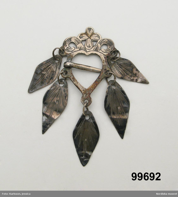 Hjärtformad sölja av silver med ornamenterat krön och 5 lövformade hängen, nål i mitten. Stämplar saknas.  Berit Eldvik maj 2006