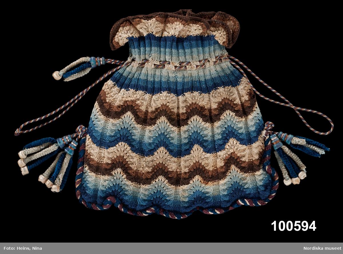 Påsväska. Maskinspunnet ullgarn och silke. Liten väska i påsmodell. Stickad i tunt ullgarn med glansiga ränder i silke. Stickmönstret bildar vertikala bårder med partier i slätstickning i ett mussellikande bottenmönster växlande med partier med aviga maskor. Färgväxlingarna bildar ett horisontellt vågmönster med tre olika nyanser av samma färg som bildar vågbanden. Upptill vid hopdragningen är det resårstickning med två räta och två aviga maskor samt två hålvarv med en genomträdd silkesnodd som drar ihop påsen och bildar handtag. Botten är kantad med grövre snodd av silke och sniljor som bildar en vågig kant. I sidorna fastsydda tofsar av silkesniljor och silkeklädda träformar. /Berit Eldvik 2002