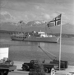 Kongeskipet Norge kommer inn fjorden med fjell i bakgrunnen.
