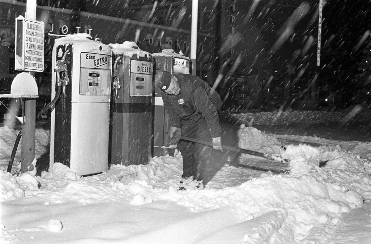 Nysnø, Oslo, 12.12.1962. Mann måker snø på bensinstasjon.