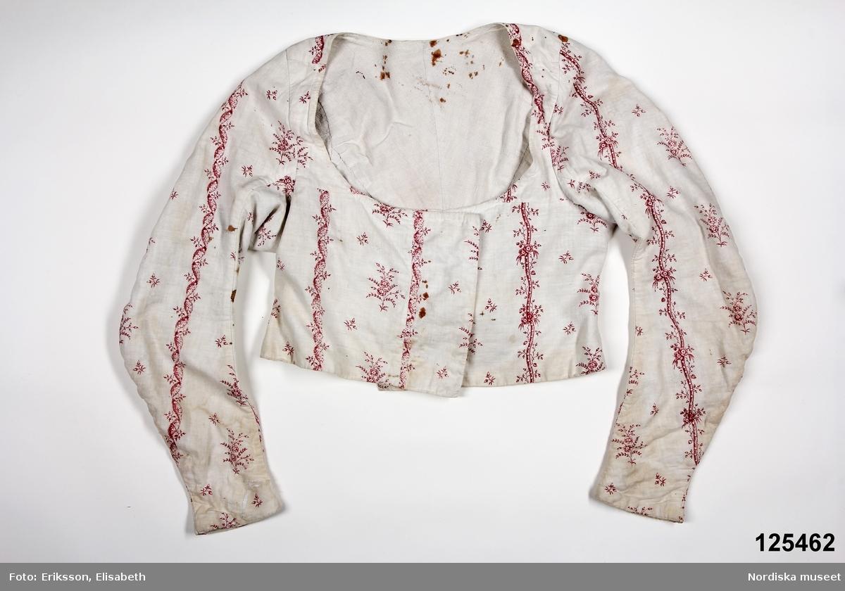 Kort tröja med ryggskört. Av vitbottnad kattun, dvs. ett fintrådigt vitt bomullstyg med blocktryckt mönster i rött. Mönstret i gustaviansk stil med  glesa blomsterbårder och mellan dem strödda kvistar med tunna blommor och blad. 2 framstycken/sidstycken med infällda skörtkilar i sidorna, vid och djup halsringning, 2 smala ryggstycken som avslutas i ett skört med 3 veck. Ovanför skörtet 2 prydnadsknappar överklädda med kattuntyget. Lång snäv ärm svängd med 2 sömmar.  Hela tröjan fodrad med vit linnelärft, något grövre i ärmarna. Framstyckena överlappar varandra men knäppning saknas. Anm. många materialskarvar, kring halsringning och på ärmarna.  En del rostfläckar, en uppriven lucka i tyget på höger ärm. samt bristning  vid skörtet. Tröjans ägarinna bör ha varit född  ca 1785-90, och bar denna innan hon var gift alltså omkr. 1810-15.  Sonen Aron föddes 1826. Uppgifterna om hemspunnet, hemfärgat och hemväft är helt fel, dessa kattuntyger trycktes på fabriksvävt tyg i speciella kattuntryckerier i städerna. Tröjan är ett bra exempel på folklig modedräkt. Tyget kan vara äldre än tröjan, möjligen återbrukat. /Berit Eldvik 2007-12-27