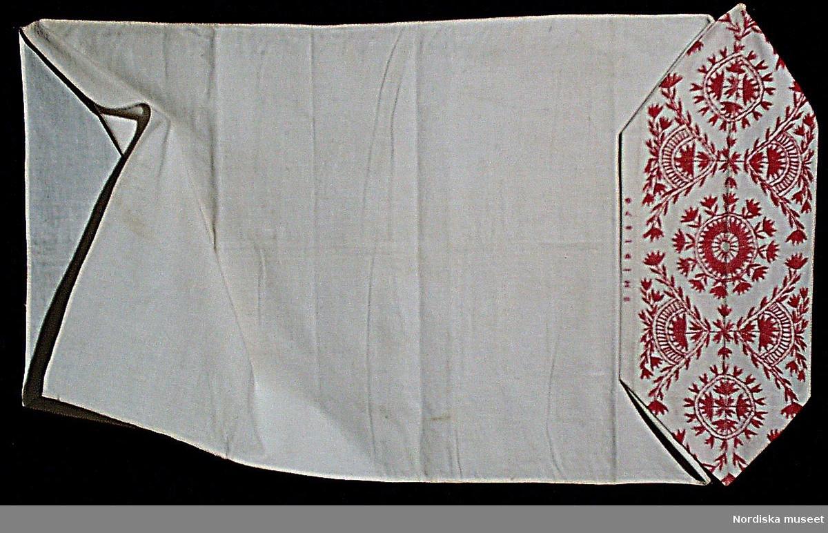 Långörngott i vit köpt bomullslärft med handsydda sömmar, fastsydd huva i bomullslärft med fritt broderi i s.k. tofssöm eller järvsösöm med rött bomullsgarn. Märkt med rött bomullsgarn i korssöm ovanför huvan B H I D 1870. Broderiet är utmärkande för Järvsö där det kallades tofssöm till skillnad mot Delsbos långsöm. Just detta mönster var det allra vanligaste från 1860-talet och det är mycket troligt att örngottet är broderat i Järvsö för att senare hamna i Bollnäs.  Berit Eldvik april 2005