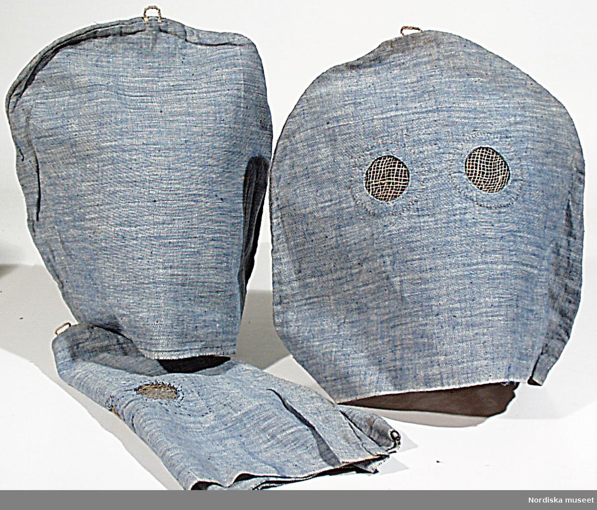 """Huvudliggare: """"Huva, ansiktsmask, tunt bomullstyg, 3 st; vit varp, blått inslag; Halvcirkelformade, något förlängda nedåt; högt upp liten garnögla; på framstycket urtag för ögon och innanför gles linneväv; helt handsydd med söm tvärs över; använts på kriminalvårdsanstalten i Mariestad. Br 37 cm, H 29 cm. G 1976 25/5 Kriminalvårdsstyrelsen, Norrköping. Mariestad."""""""