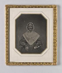 Porträtt av sittande äldre kvinna. Knäbild, en face. Klädd i