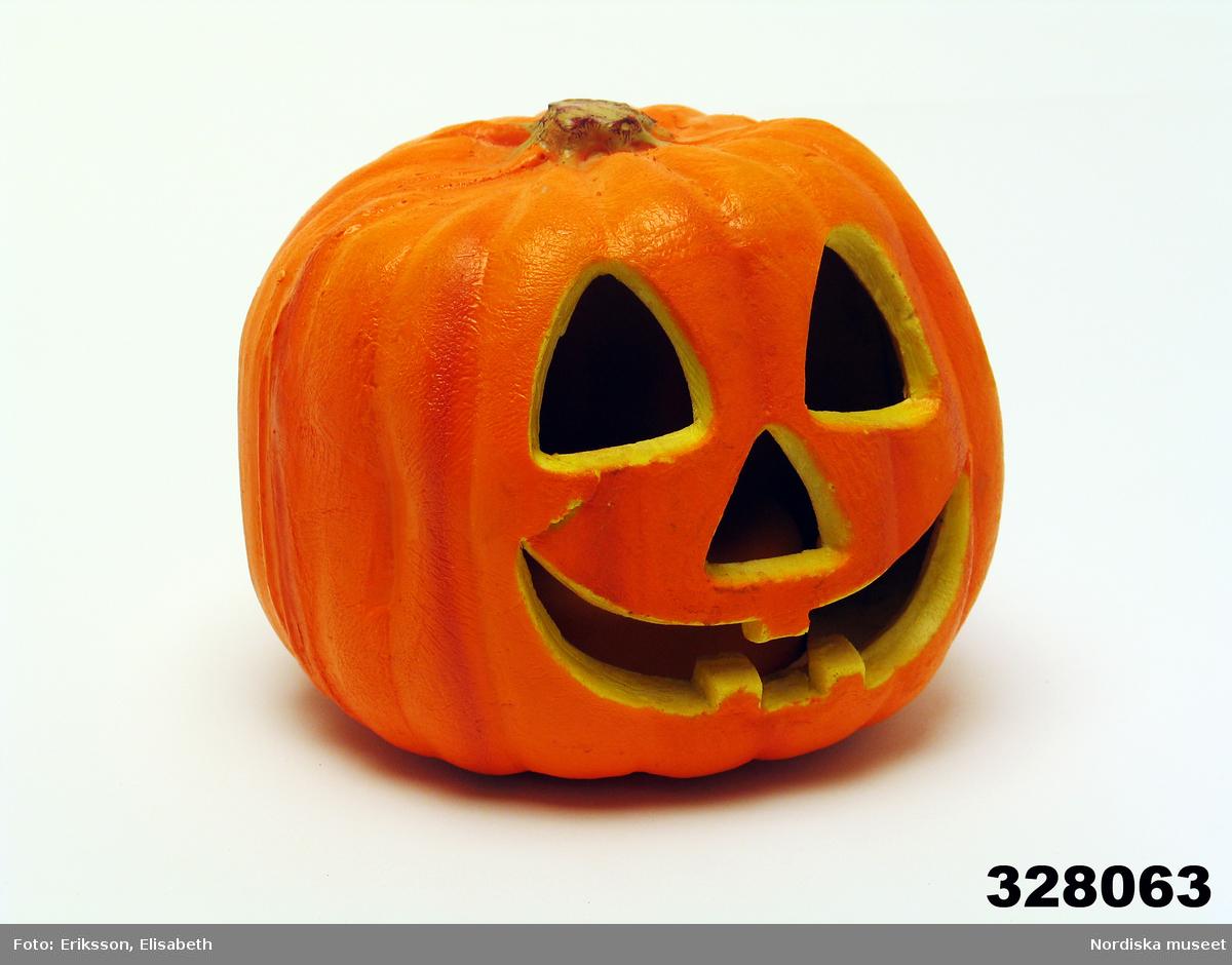 """Huvudliggaren: """"Lampa, halloweendekoration, i form av en pumpa, batteridriven, blinkande ljus. Polystyrencellplast, utskurna hål f ögon, näsa o mun, orange utsida, gilinsida. I botten dosa av orange hårde plast m liten glödlampa o lucka f 3 st 1,5 V-batterier. Anv Andrea Wolde (f 1965) 2002. H 15 cm diam 17 cm. Spricka i höger sida o under vänster ögonhål; några färgbortfall. I[nköpt] 14/11 2002 från Andrea Wolde Bryggargatan 6B Stockholm [tillsammans med] 328.033 - 328.083. [...]."""""""