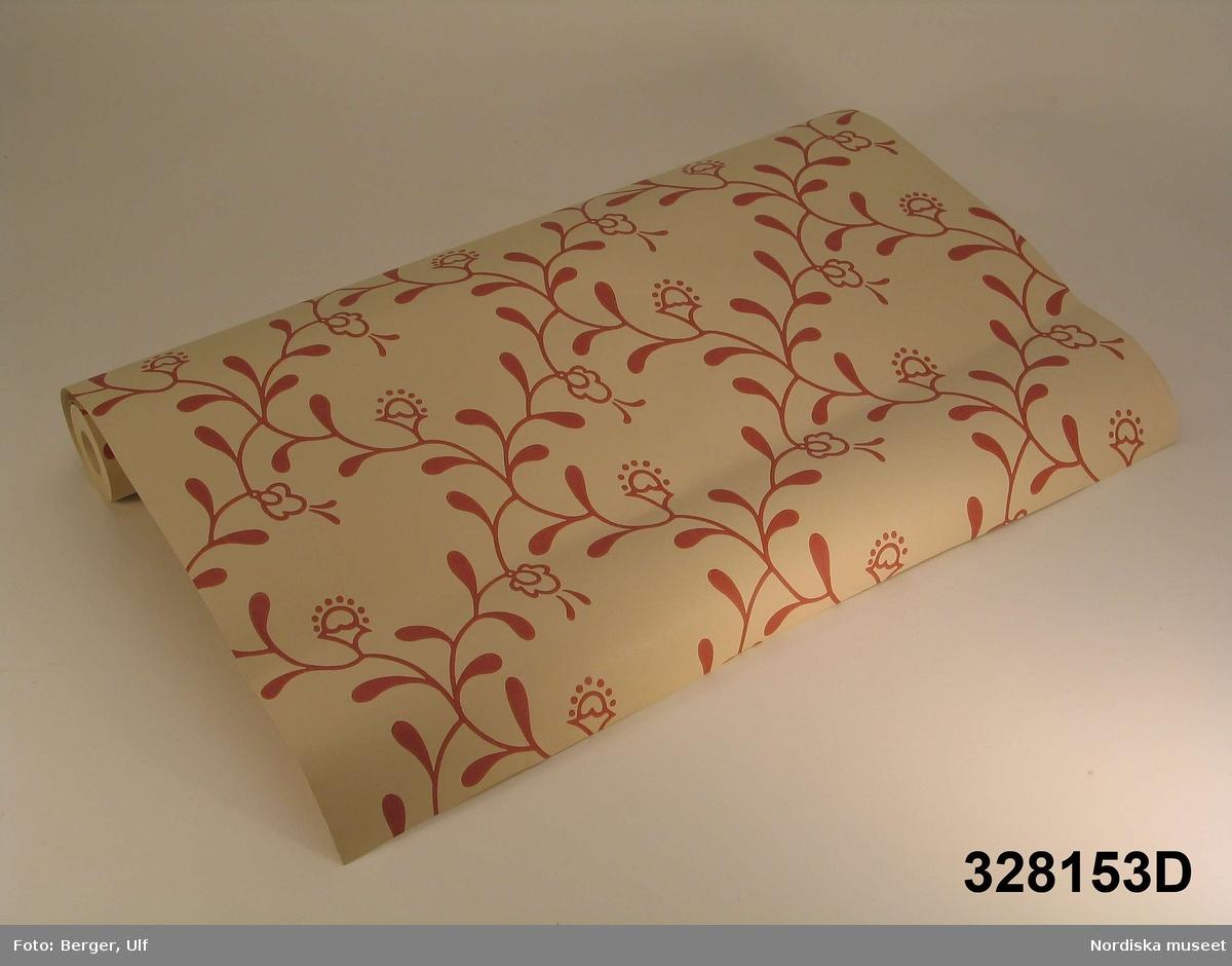 """Papperstapet, 4 rullar, maskintryckt på ljust genomfärgat papper. Ytmönster av snedställda rutor bildade av mjuka stänglar med blad och blommor mot ljusbeige, närmast vit, botten.  A = mellanblått ytmönster B = gult ytmönster C = svart ytmönster, ljust brunbeige bottenfärg D = rött ytmönster  Tapetmönstret ritat av arkitekt Uno Åhrén för Hemutställningen på Liljevalchs 1917. 1976 tog tapetfabriken Duro upp mönstret i sin produktion, sedan de 1968 börjat ta fram gamla tapeter för nytryck tillsammans med Riksantikvarieämbetet, så kallade Gammalsvenska tapeter. Tapetmönstret döptes till Elsagården av Duro.  I 1985 års upplaga av Gammalsvenska tapeter var tapeten färgsatt i den tidens blekare färger, bl.a. ljusgrönt och ljusrosa. I den upplaga av Gammalsvenska tapeter som kom ut 1991 fanns Elsagården inte med, men den återkom 1999, färgsatt enligt de kända originalen, mellanblått, gult och svart samt i en ny röd färgsättning. Den röda varianten togs fram tillsammans med pensionerade riksantikvarien Åke Nisbeth, som strävade efter att göra den röda nyansen så trogen 1917 som möjligt.  Tankarna vid nytryck av tapeter har varierat med tiden. 1976 eftersträvade Duro autentisk färgsättning, medan det 1985 var mera efterfrågan på färger som var moderna. I dag (2003) upplever Duro att människor är mera medvetna om inredningsstilar och vill ha autentiska tapeter, gärna från den tid då deras hus byggdes.  Till varje tapetrulle fanns en lös informationslapp av papper med tapetens namn, artikel- och serienummer, uppsättningsanvisning, information om rullens längd och bredd, att den är förklistrad, högtvättbar, har mycket god ljusäkthet och kräver rak passning (ett ex kopierat och lagt som bilaga till huvudliggaren).  Jfr ett original av samma tapet inv.nr 328.152. Maria Maxén 2004-04-14  Katalogkort: """" a) rullens H ca 10,0 cm, B 53,0 cm, tapetens H 1000,5 cm, B 53,0 cm. b) rullens H ca 10,0 cm, B 53,0 cm, tapetens H 1000,5 cm, B 53,0 cm. c) rullens H ca 10,0 cm, B 53,0 cm, tapeten"""