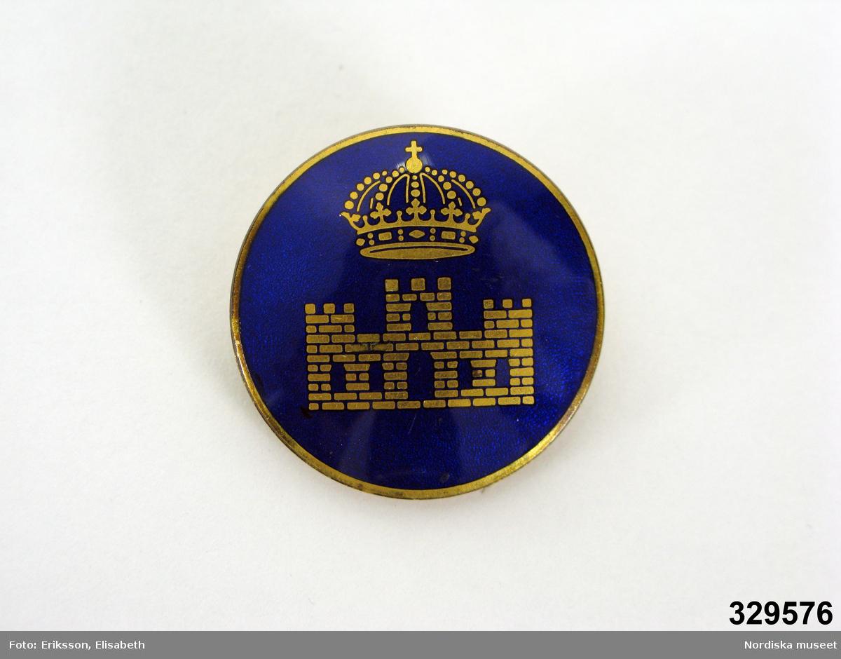 Rund, emaljerad brosch i gulmetall med fastsättningsnål på baksidan.  Framsidan emaljerad med blå botten med guldfärgat figurmotiv i form av en sluten krona med en fängelsebyggnad under.   Ingår i en ämbetsdräkt, modell 28, för kvinnlig överkonstapel vid svenskt fängelse. Övriga dräktdelar; klänning, hatt, strumpbyxor och skor (se inv.nr 329.572-329.576).  Ingår i ett större förvärv av föremål från svenska fängelser. /Cecilia Hammarlund-Larsson 2009-08-27