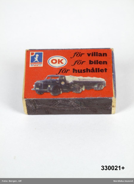 """Tändsticksask av papp och trä, plån på långsidorna, med instickslåda. Blå. Påklistrad röd etikett med reklamtryck på ovansidan i form av en tankbil och text: """"OK / för villan / för bilen / för hushållet"""". I övre vänstra hörnet en bild på en tändsticksask med """"Solstickepojken"""". Asken är tom.  Asken är beställd av OK (Sveriges oljekonsumenters riksförbund) som bl..a hade bensinmackar runt om i Sverige. Det ingår idag i företaget OKQ8.   Tändsticksasken är tillverkad av Svenska Tändssticks AB omkring 1950-talet.   Solstickepojken, ritad av Einar Nerman för stiftelsen Solstickan 1936, samma år som stiftelsen grundades. Stiftelsen har ett nära samarbete med Tändsticksaktiebolaget/Swedish Match.   Under 1900-talet användes ofta reklam på  tändsticksaskar/tändsticksplån i marknadsföringen av olika varor och tjänster. Askarna/plånen delades ofta ut gratis och många restauranger lät dem ligga framme på borden för gästerna. Under slutet av 1900-talet blir detta mindre populärt, delvis för att tändaren blir vanligare, men framför allt beroende på att färre rökte och att rökning inte längre förknippades med något positivt.  Tändsticksasken ingick i en större samling som ihopsamlats av givarna under sina bilresor under 1950-talet och fram till 1980-talet inom och utom Sverige. Ett urval ur samlingen gjordes av Nordiska museet 2009. /Leif Wallin 2009-09-24"""