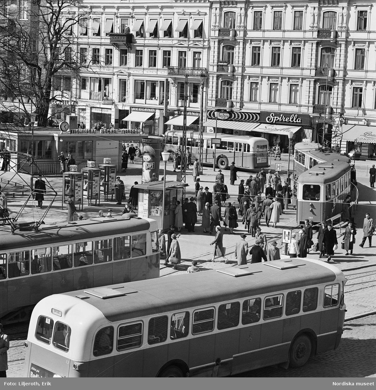 Vy över Gustav Adolfstorg i Malmö. En myllrande trafikbild med bussar, spårvagnar och fotgängare. I fonden husfasader med butiker, bland annat Spirella.