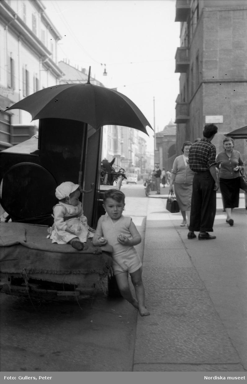 Liten flicka och pojke på gata i Italien. Kärra. Flyttlass.