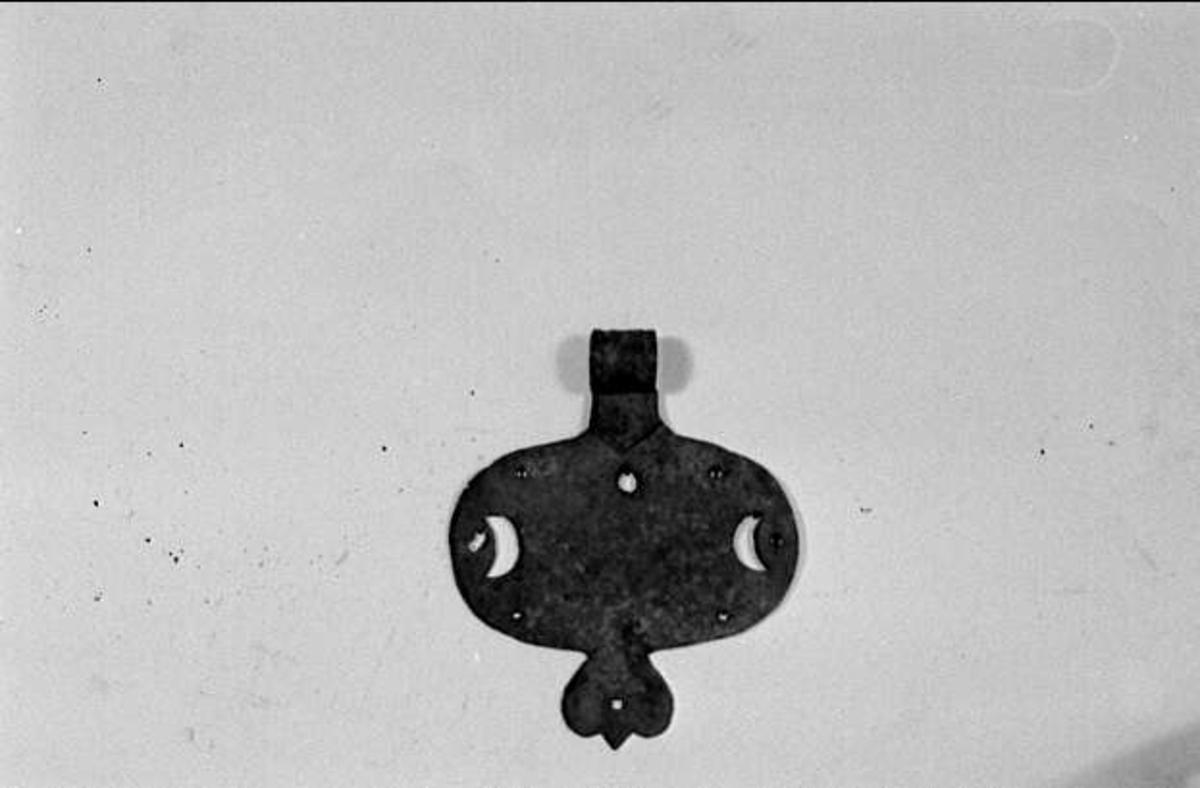 Dörrbeslag av järn av typen vertikalt plattgångjärn. Ovalt beslag med utskurna halvmånar. Ornamenterad gångjärnsände av enkel rulltyp.