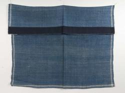 Halskläde av blå kypertvävd linne med vit rand runt kanten. I ett hörn märkt I O med blå korsstygn. Fållad på två sidor, på den ena ett blått band fastsytt på baksidan efter märkningen.