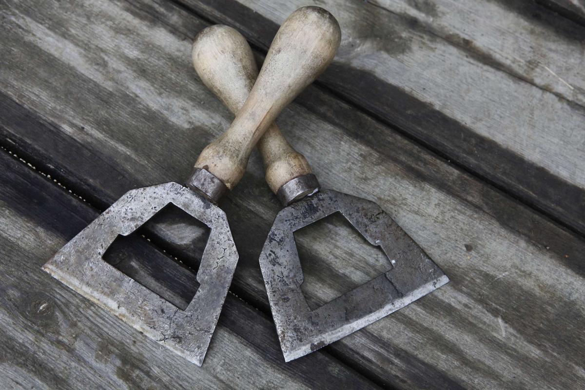 Två hackknivar av järn, med handtag av trä.