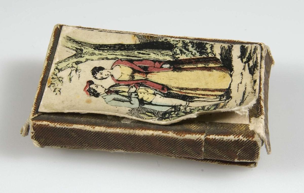 Ask av papp, guldkanter. Motiv med ungt par i gult, rött, grönt på vit grund.