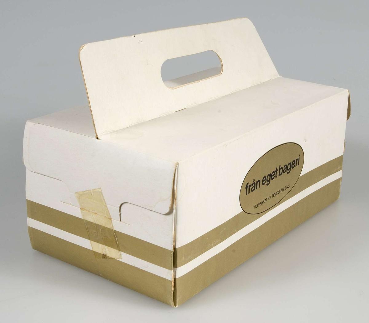 Kartong för semlor och bakelser av vit papp med uppvikt flik med urtag för handtag. Två guldränder runt och oval i guld med text: från eget bageri tillverkat av Tempo-Åhléns.