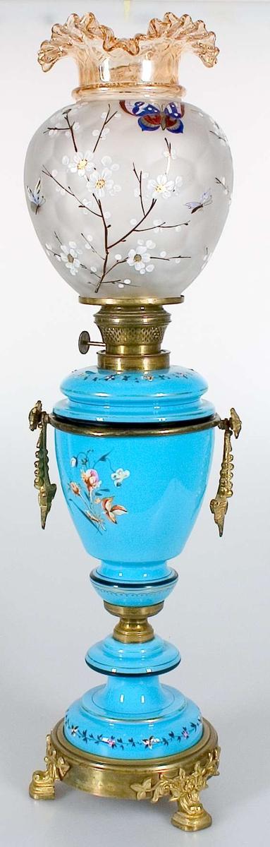 Fotogenlampa med fot av blått glas och gulaktig metall. Utsmyckning i form av målade blommor i flertal färger, bland annat kransar runt foten. Lampkupa av delvis opakt glas, målad med blommor och fjärilar i japaniserande stil.