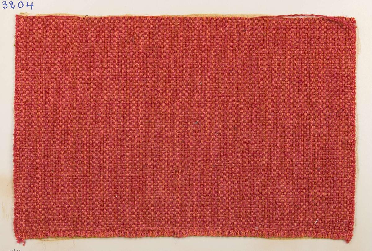 """Vävprov ämnat för möbeltyg vävt med bomulls-, ull- och lingarn i vävtekniken panama, rött. Vävprovet har nummer """"B-3204""""."""