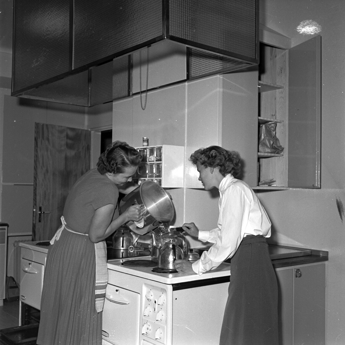 """Husmor Anne-Marie Alsén och hembiträdet Ingrid Pettersson """"i full fart i det rymliga köket"""", pojkhemmet på Repslagargatan 16, Svartbäcken"""