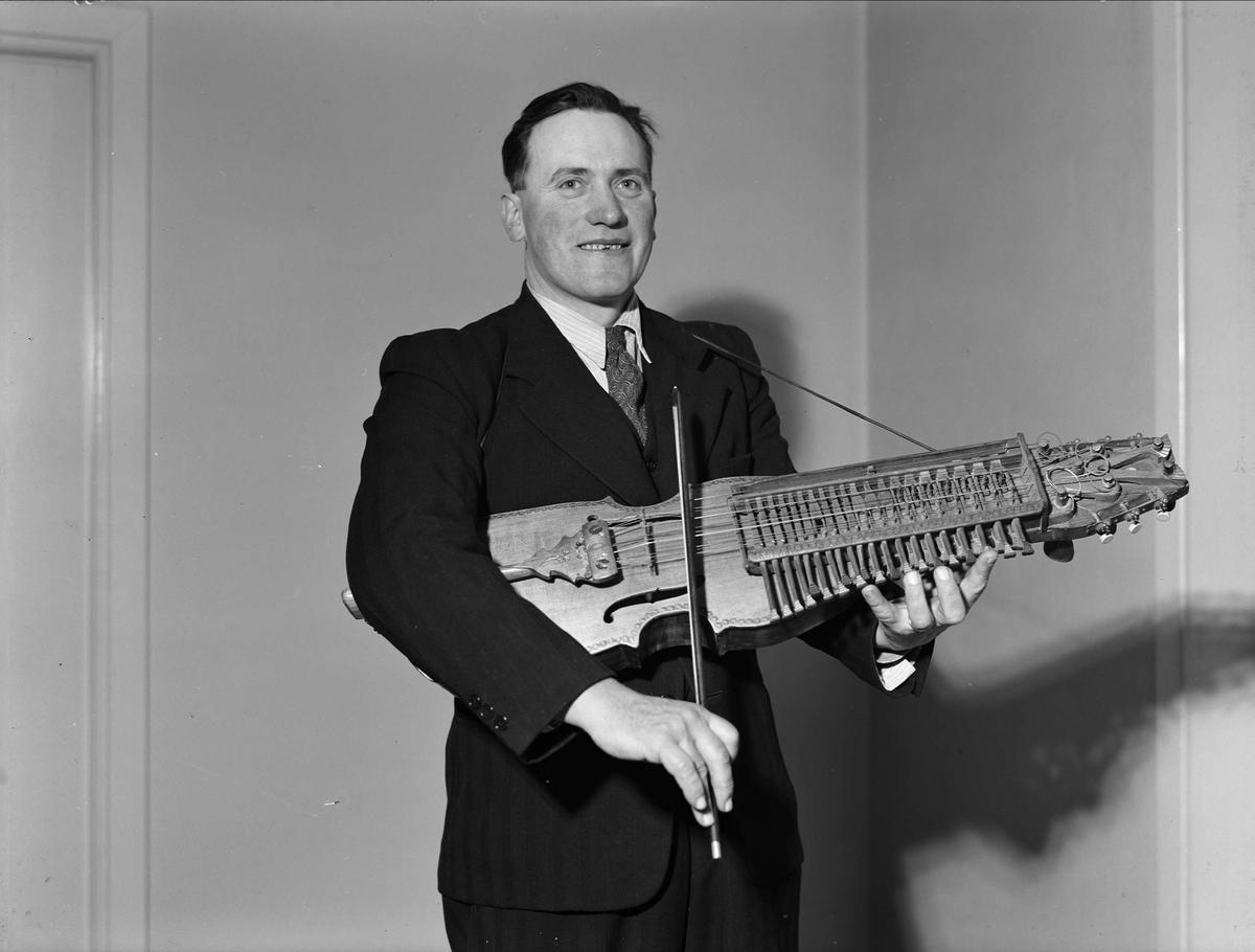 Spelmannen Eric Sahlström med nyckelharpa, sannolikt Uppsala, december 1949