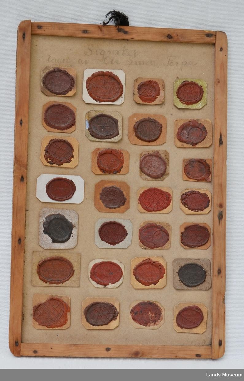 28 stk av O.Smeds lakksignetter montert på papplate med treramme.