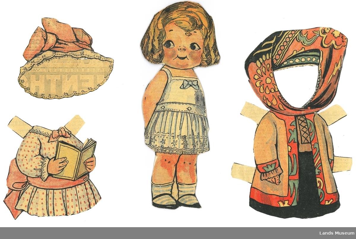 Papirdukke med klær som klipt ut frå avis/magasin. Dukken er montert på papp.  A- dukke, 20,5 cm x 9 cm B- kosakk-kåpe, rød, grønn, gul, beige og svart, 19 x 10 cm C- kjole med rosa prikker og sløyfe, bok, 9 x 9 cm D- hatt, rosa og kvit, 8 x 9,5 cm