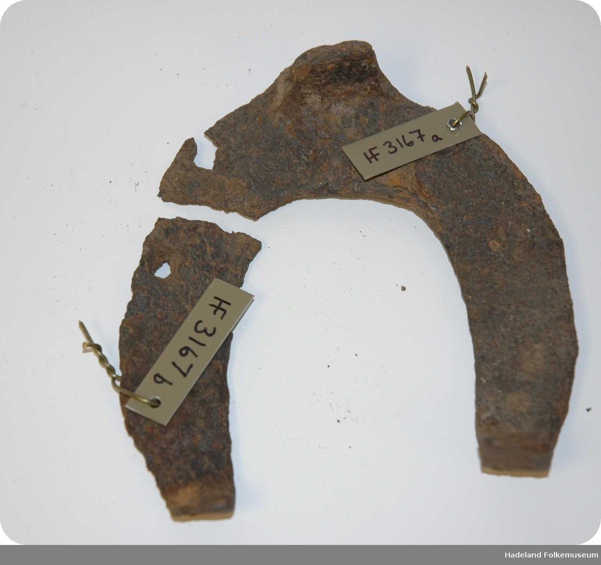 Hestesko av jern. En U-formet beskyttelse som legges utenpå hestens hov for å hindre at den slites ned for fort. Denne har 4 synlige sømhull, tåkappe og er brukket i to på venstre side.