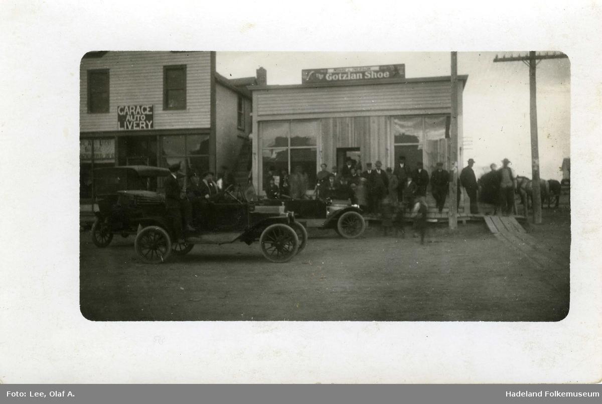 Gateparti, tre biler parkert foran to butikker. En stor gruppe mennesker foran ene butikken.