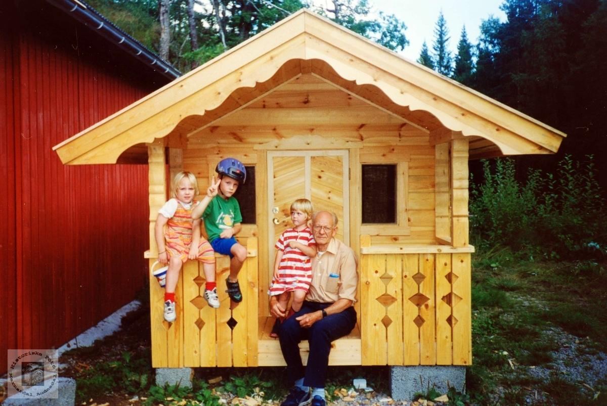 Bestefar Halvor Flottorp med barnebarn ved lekestua han har laga.