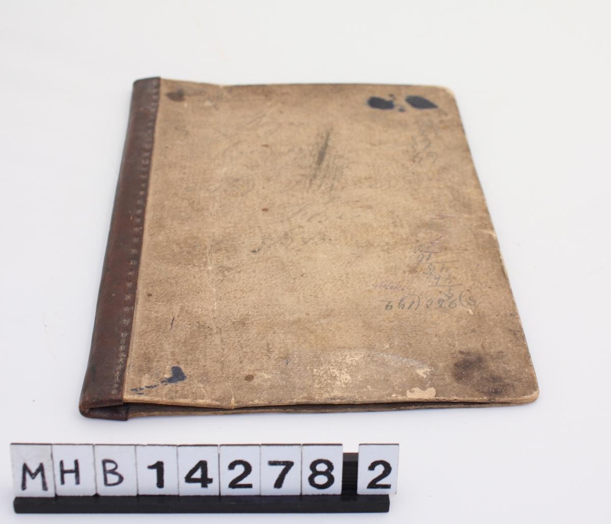 Etui som ligner et bokomslag. Det består av to rektangulære papplater som er forbundet med hverandre i en langside med en påsydd lærremse. Det er diverse påskrifter og utregninger på papplatene, som er vanskelige å tyde.