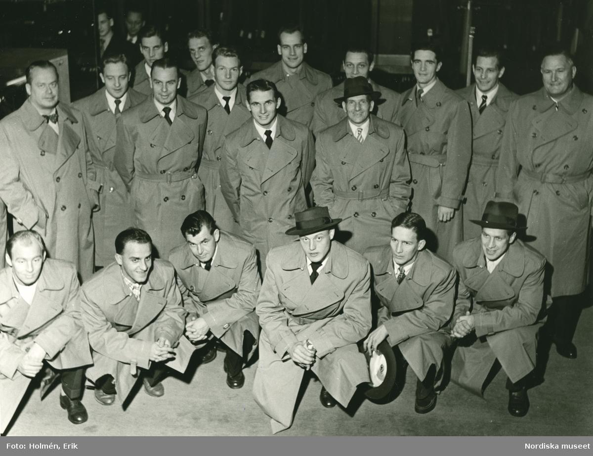 Grupporträtt av män i rockar. Troligtvis svenska herrlandslaget i fotboll, tidigt 1950-tal. Putte Kock längst till vänster i mittersta raden, samt Kalle Svensson sittandes i mitten.
