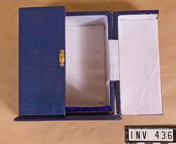 """Samhörande nr är 294-299, 321-350, 400-448 (435-436). Fodral t minnestecken. Från ingenjörtruppskolan i Poona (Pune), Indien. Överlämnat 1975-01-25 under CA besök vid indiska arméni Poona ( jan 1975. """"From Maj.Gen. K C Soni, AVSM, Commandant, Commandant, College of Military Engineering, Pune."""" Asken i blå klot är utformad som ett litet skåp med två dörrar, som låses på mitten med ett litet spänne. Invändigt klätt med vitt konstsiden och botten med blått sammet. Mått, botten: 115x85 mm, asken: 120x70 mm."""