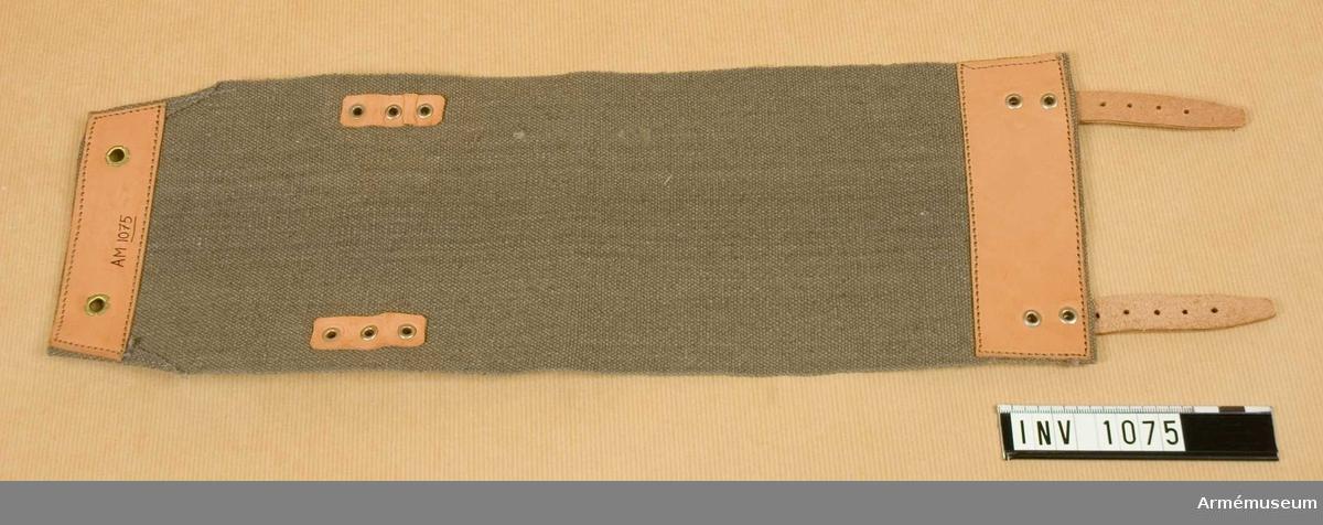 Av gråbrungrön smärting. Kortsidornas insidor är förstärkta med ljust läder. Ena sidan är försedd med två ljusa läderremmar, vilka är fastsatta med två metallnitar. Motsvarande sida på damasken är försedd med två spännen. Avigan förstärkt med ljust läder vid ändarna. Ytterst på den ände där spännena sitter finns två öljetterade hål. Damasken är avsdd att sitta nedtill över byxan och sammanhålla den över skodonet. Har tillhört mob.utrustning vid museet.  Samhörande nr är 1074-1129, 8240, (1074-1075).