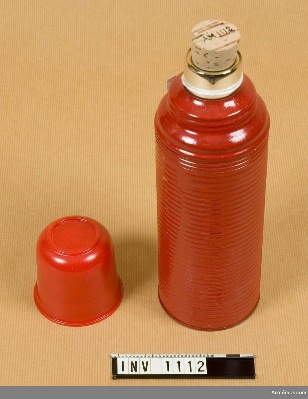 """Komplett. Utförd som ett dubbelväggigt glaskärl med lufttomt mellanrum och försilvrade väggar, varigenom värmeutbyte med omgivningen förhindras.   Glaskärlet skyddas av ett rödmålat metallfodral med påskruvbart lock i form av en bägare. Locket, dvs hatten, är avsedd att drickas ur. Muggen är utförd i bakelit. Bägaren märkt invändigt med """"W"""".   Höljet är isärskruvbart så att glasbyte kan ske. I botten finns två avrinningshål. En kork avpassad till halsöppningen hör till. Termosen förvaras i kartong av wellpapp."""