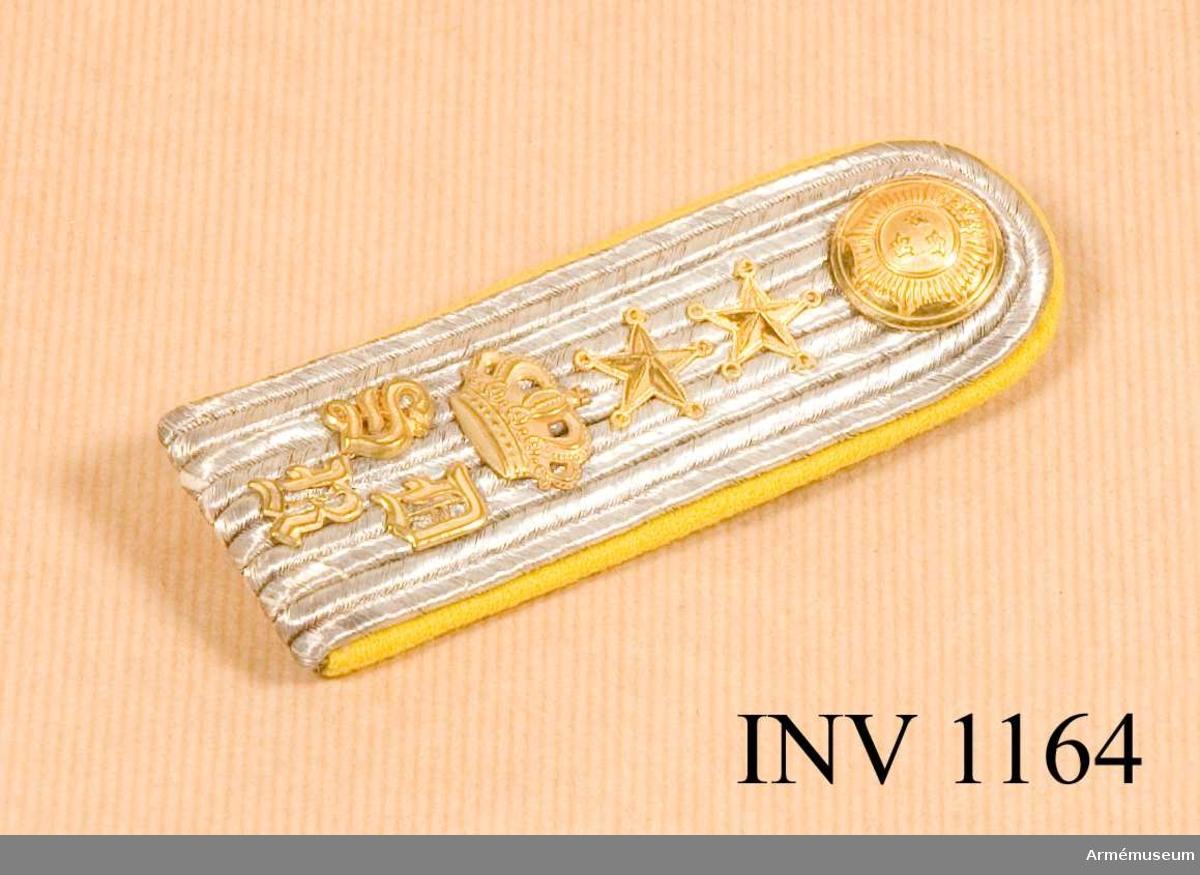 """Av silvergaloner, tätt lagda i fem rader. På dem närmast axelsömmen """"SRD"""" under kunglig, sluten krona. Två stjärnor och regementets knapp m/1854, allt i guld. Klaffen är fodrad med gult kläde som går fram över ovansidan som en kant. Baksidan har en mässinghake märkt """"MILITÄREKIP.AKT.BOLAG. MEA"""". En hank för fastsättning i gult kläde. Källa: Arméns rulla 1908."""