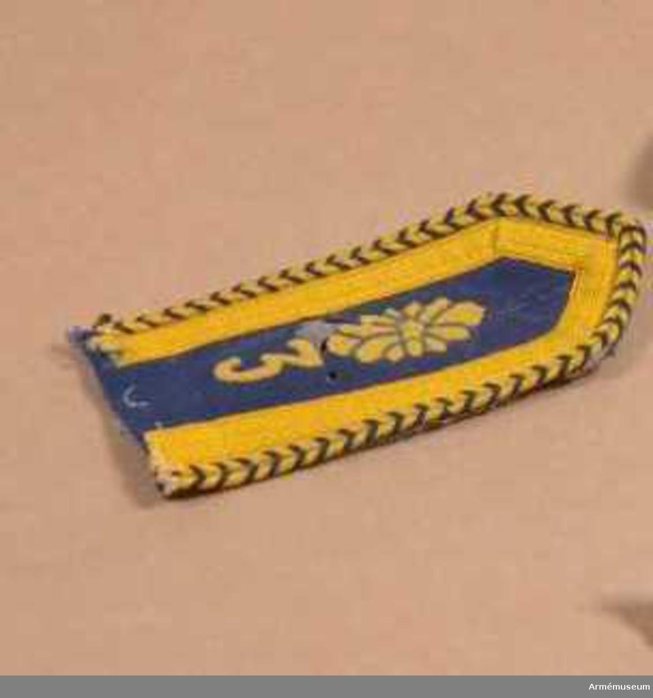"""Mått: 140 x 65 mm.Axelklaffen har matta av mellanblått kläde med gula redgarnsband utmed kanten och med """"studentsnöre"""" utmed ytterkanten. Snöret är flätat av blått och gult redgarn.  Ingenjörkårernas gula kårmärke sitter strax nedanför knapphålet och innanför det sitter en trea i gult kläde.  Axelklaffen har foder i grått kläde."""