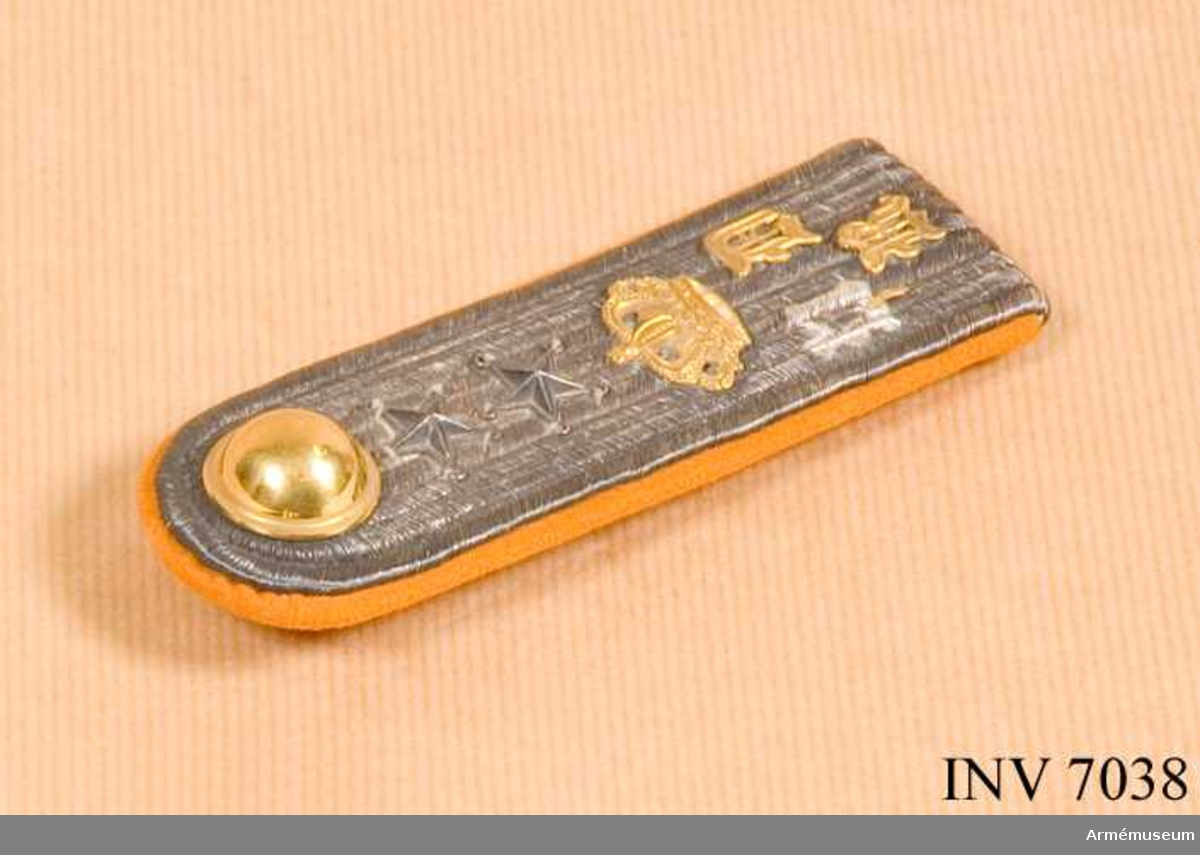 Matta och foder av orangerött kläde belagd med silvergalon i fem rader. Två silverstjärnor, gradbeteckning för löjtnant i reserven vid K 4. Förgylld knapp vid axeln, sfärisk. Förgylld krona och bokstäverna N D R, även de förgyllda.Haken på undersidan är märkt MEA d v s  Militärekiperingsaktiebolaget.Till vapenrock m/1895. Gott skick. Silvret är oxiderat.