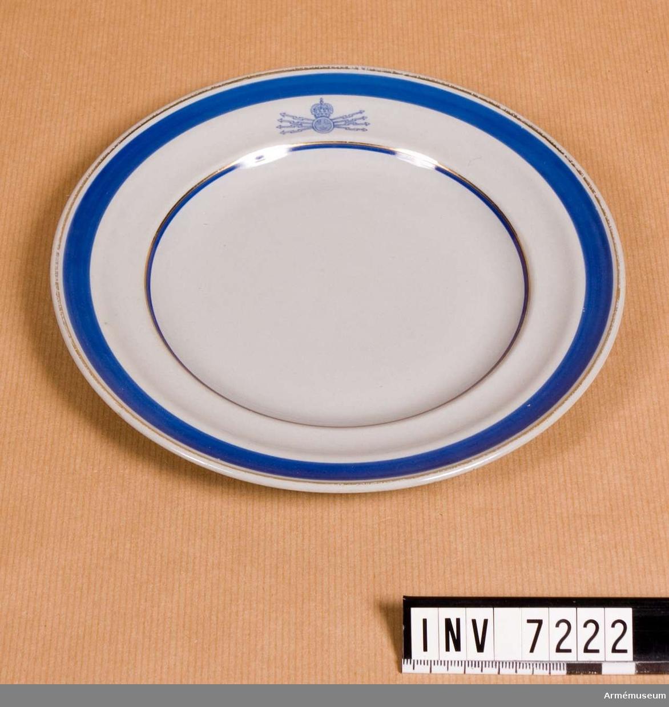 Assiett, Fälttelegrafkåren. 1934. En grå assiett med dekor i blått och guld och med  Fälttelegrafkårens emblem. Färg grå, blå, guld Q,L,D.