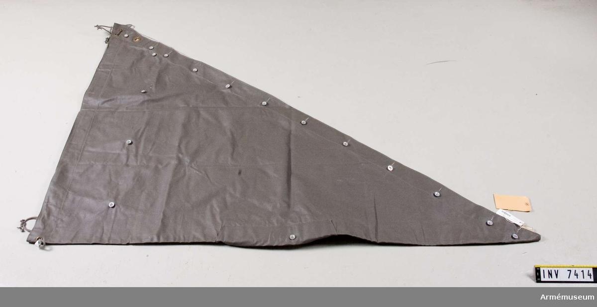 Triangelformat och avpassat som tältdel med knappar och knapphål. Hål för att trä igenom huvudet då delen används som regnskydd. Färg grå Q.