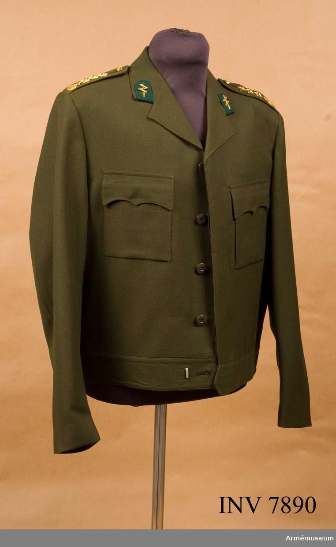 Tillverkad av olivgrönt tyg, har enradiga slag, är gylfknäppt, har fasta axelklaffar samt bröstfickor med fasonerade ficklock. Kragspegeln bär ingenjörtruppernas samt väg- och vattenbyggnadskårens gröna underlag för truppslagstecknet i form av en blixt över ett svärd. Axelklaffarna har Upplands vapen, tre stjärnor betecknande kapten samt knäpps mot  regementets knapp m/1960 mindre. Storlek C 50.