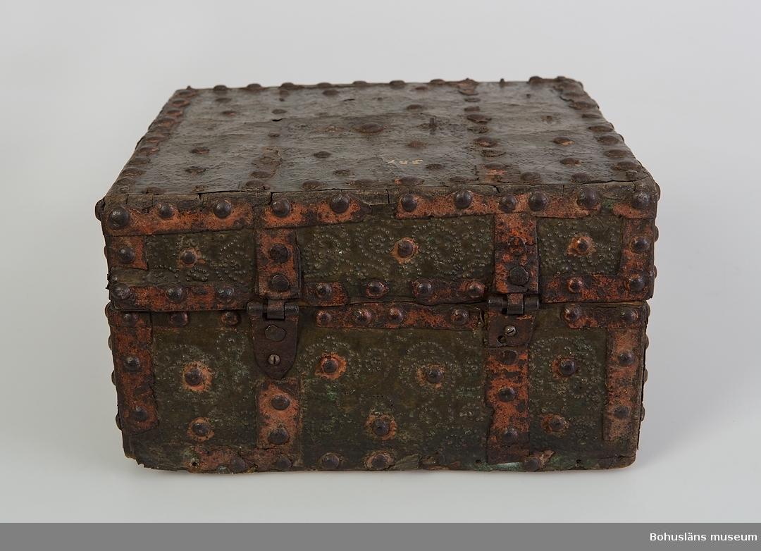 """Kassaskrin av trä, nästan fyrkantigt, med platt lock, metallbeslaget. Tillverkat under 1600-talet. Skrinet har tillhört Gesäters kyrka i Dalsland och primärt använts som kyrkokassaskrin.  Metalldelarna är av olika slag. Mässingsplåt täcker skrinets hela utsida, förutom undersidan. Mässingsplåten är punsdekorerad och hålls på plats av fastnitade dekorband av järn. Järnband och nithuvuden är en del i mönstereffekten. Spår av röd färg finns på järnbanden. Nitar, nithuvuden och lockets handtag saknas.  Inuti locket står årtalet """"1786"""" i vitt samt """"Hilma Carolina 1880"""" skrivet i blyerts. Kistebrev har funnits inuti locket. Nedre delen har varit uppdelad i nio fack. Nyckelskylt saknas. Gångjärnen är sekundärt skruvade. Plåten är defekt.  Se Knut Adrian Andersons """"Katalog I, A. yngre föremål"""", under Uddevalla museum/förening D 2A:1 i arkivet.  Ur handskrivna katalogen 1957-1958: Kyrkokassa-skrin Bottenmått: 24,5 x 25,5. H: 14,5. Träskrin med plåt- och järnbeslag. Skadad bl. a. saknas lås. Maskhål. Gesäters k:a, Dalsland 18"""
